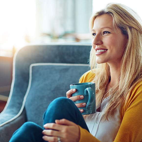 Happy woman drinking coffee to promote household insurance broker Full-time Cover