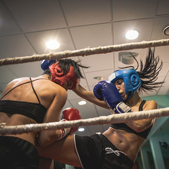 Two female boxers in action during a round to promote leading boxing insurance broker Full-time Cover