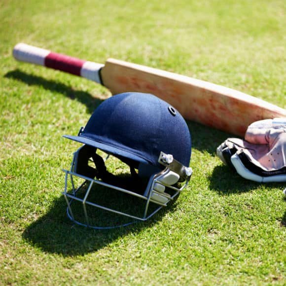 Cricket equipment on field to promote leading cricket insurance brokers Full Time Cover