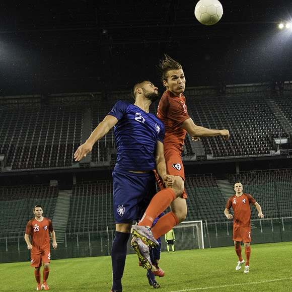 Footballers collide to hit ball on pitch to promote leading football insurance broker Full-time Cover