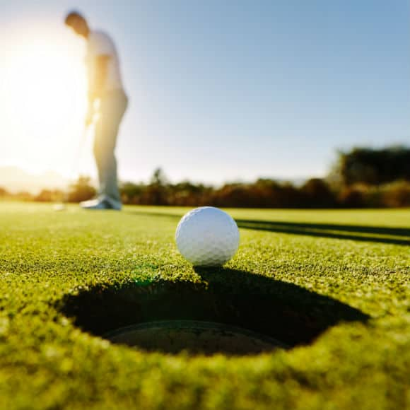 Golf ball teetering on hole to promote leading golf insurance brokers Full Time Cover