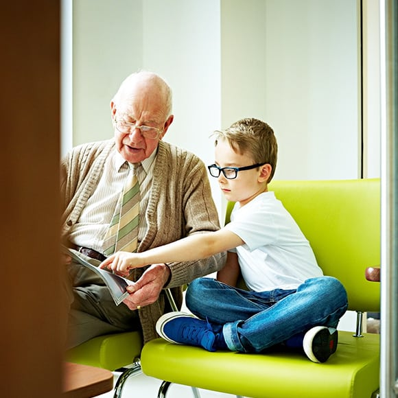 Granddad sharing magazine with grandson to promote health and life insurance broker Full-time Cover