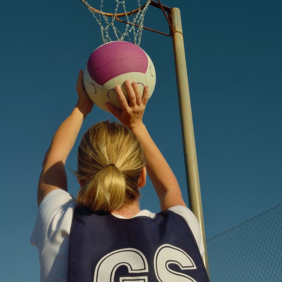 Netball player aiming at goal to promote leading netball insurance broker Full-time Cover