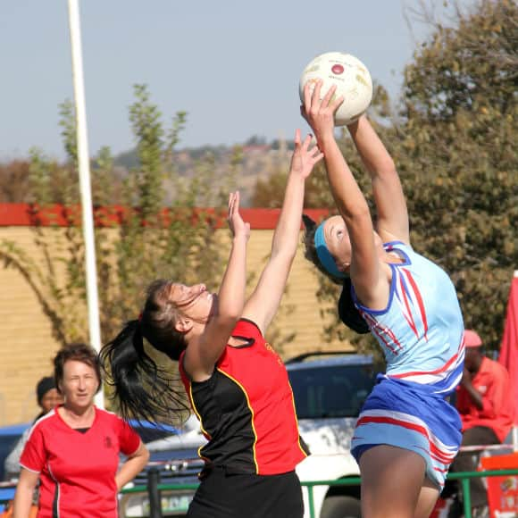 Netball player aiming ball at goal to promote leading netball insurance brokers Full-Time Cover