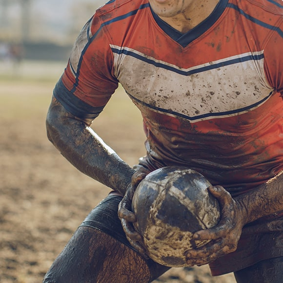Muddy rugby player crouched with ball to promote leading rugby insurance broker Full-time Cover