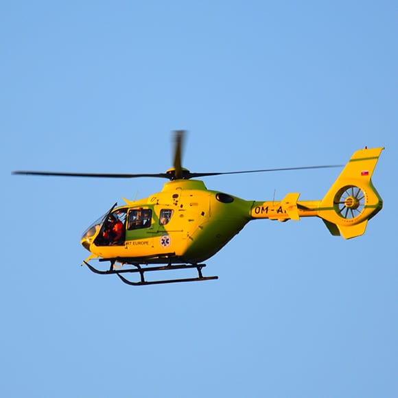 Emergency helicopter flying through blue sky to demonstrate Full Time Cover Insurance Broker's Topup Travel Insurance