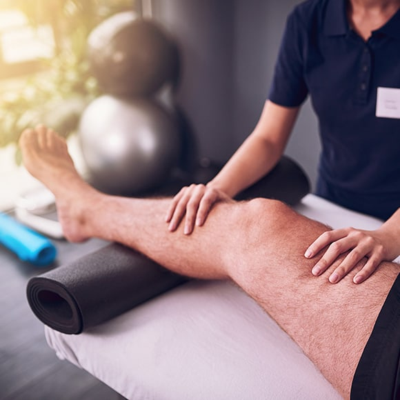 Male leg being tended to in physiotherapy session to promote Full Time Cover's Sports Accident Insurance