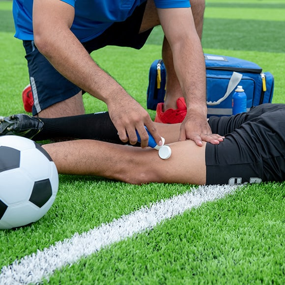 Male leg being tended to on football pitch to promote Full Time Cover's Sports Accident Insurance
