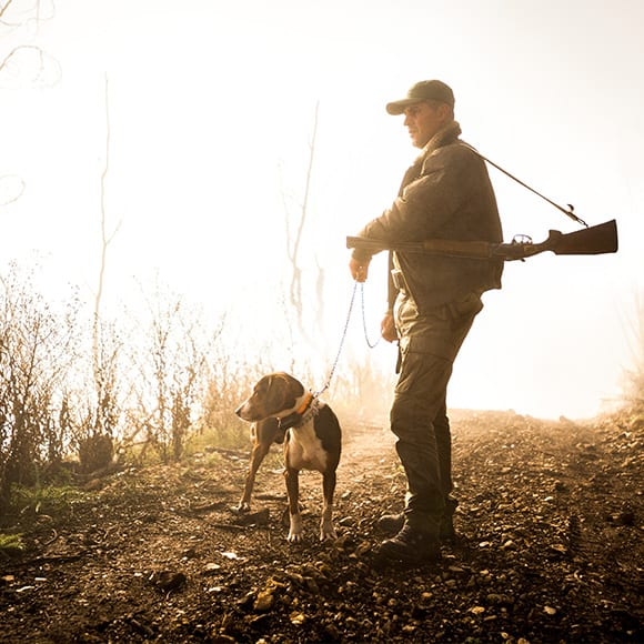 Male walking in field with gundog to promote Full Time Cover's Sports Shooting Insurance