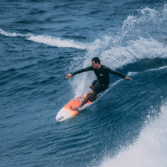 Male riding a wave while surfing to promote Full Time Cover's Sports Travel Insurance