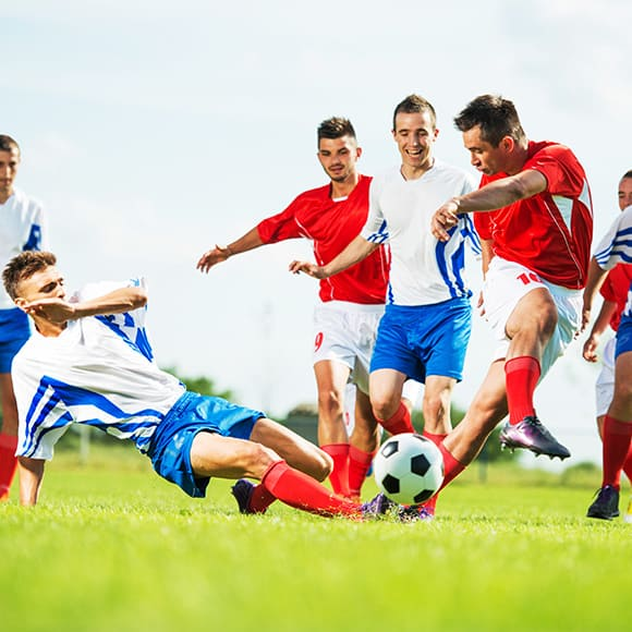 Multiple footballers going for the ball mid to promote Full Time Cover's Team Personal AccidentInsurance